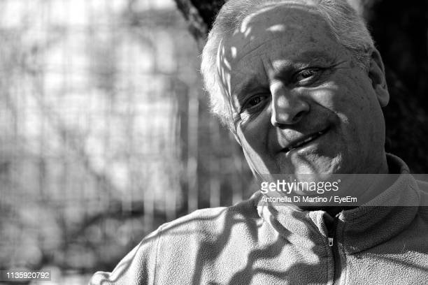 man looking away with shadow and sunlight on face - antonella di martino foto e immagini stock