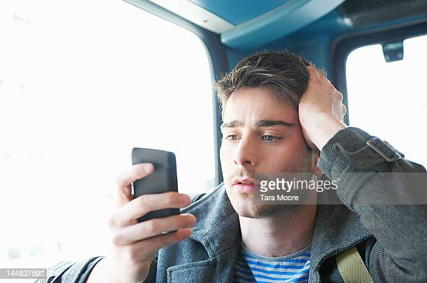 man looking concerned with mobile on bus