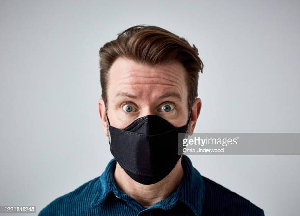 man looking directly at the camera, looking very worried and scared, wearing face mask during the pandemic lockdown - protective face mask stock pictures, royalty-free photos & images