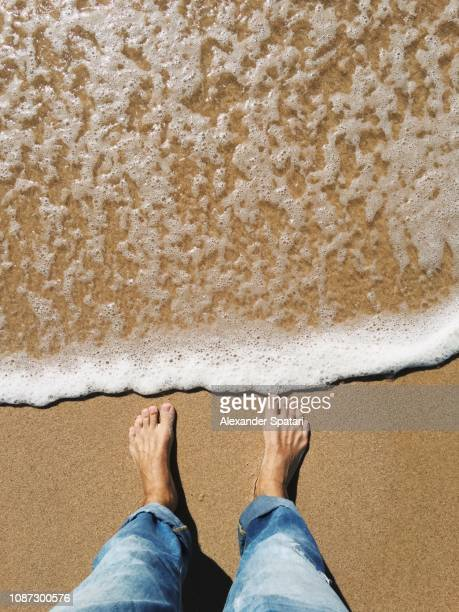 man looking down at his feet covered by sea wave on the beach - homem costas imagens e fotografias de stock
