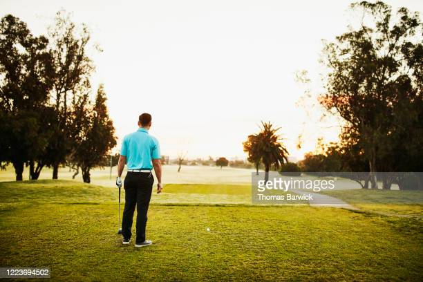 man looking down fairway before hitting tee shot while playing golf - teeing off stock pictures, royalty-free photos & images