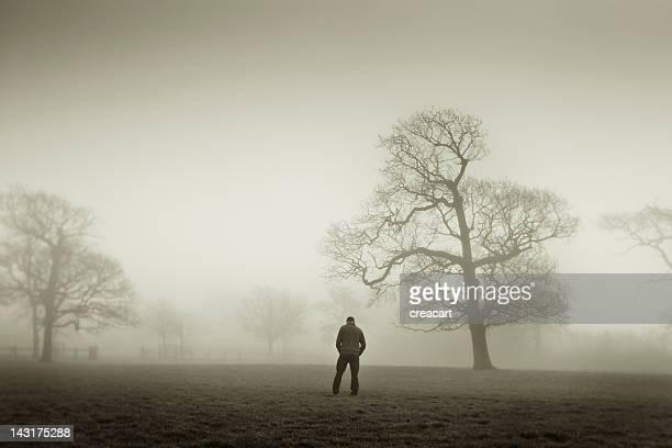Man looking down in a foggy landscape