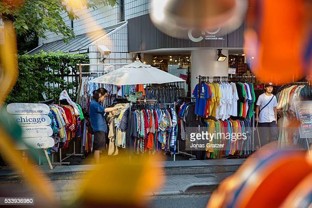 A man looking for clothes at a second hand store in Tokyo Japan