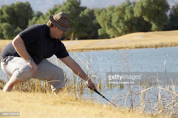 Man Looking For Golf Ball in Pond