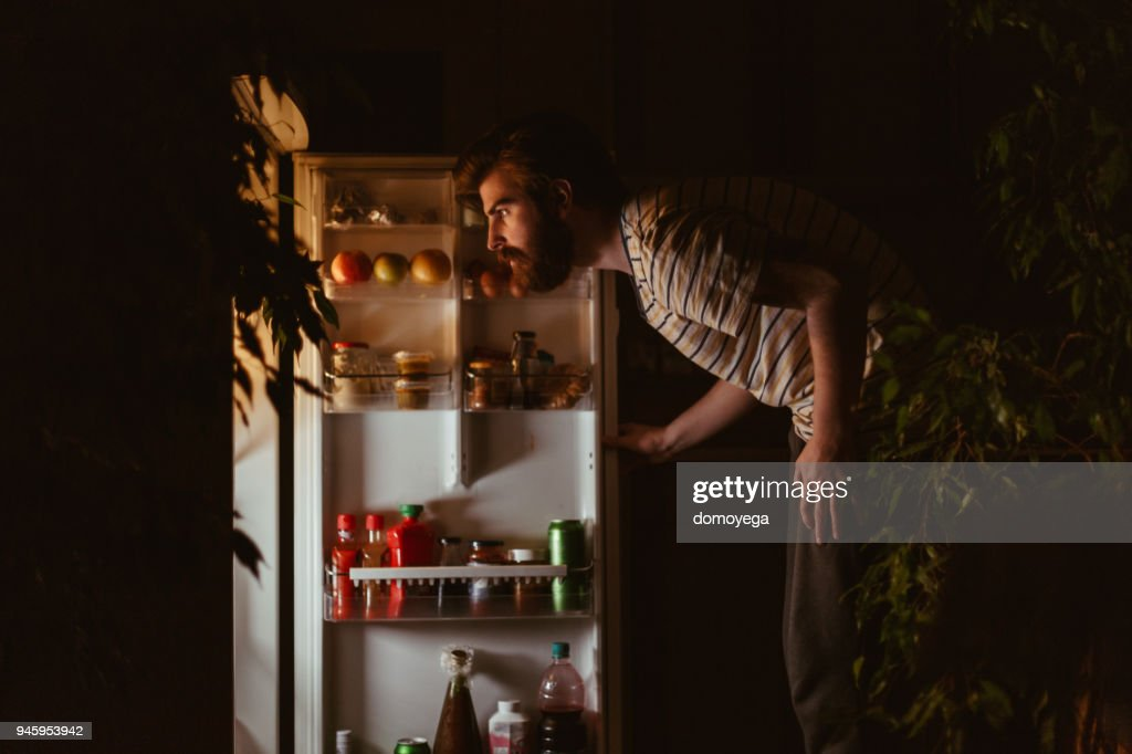 Man looking for snacks in the refrigerator late night : Stock Photo