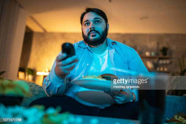 man looking for something interesting on tv - changing channels stock photos and pictures