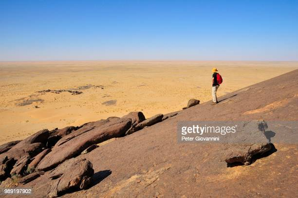 Man looking from Aicha monolith towards the flat desert, Adrar region, Mauritania