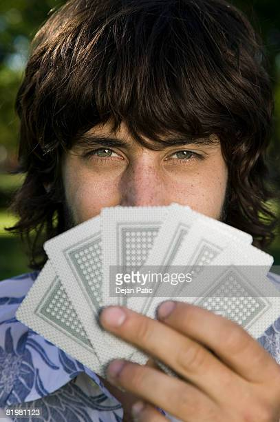 A man looking from behind a hand of cards