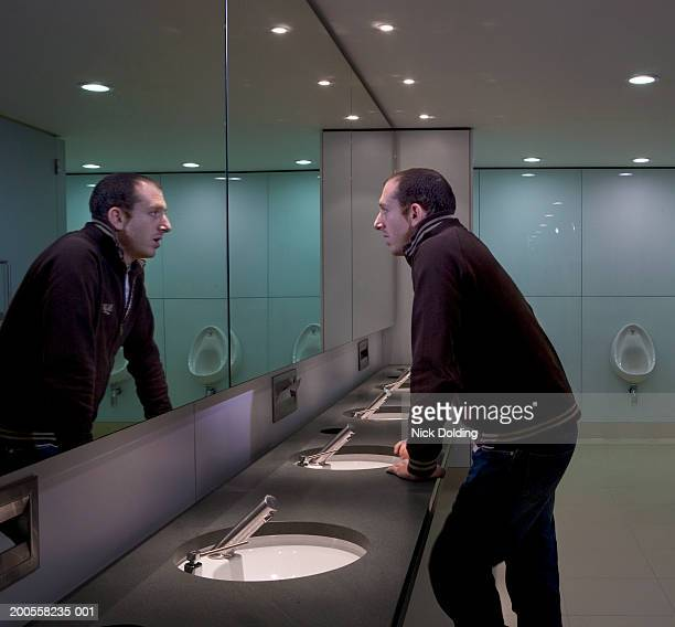 Man looking in bathroom mirror