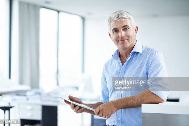 Man looking in camera while working on his tablet