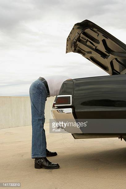 Man Looking in Car Trunk