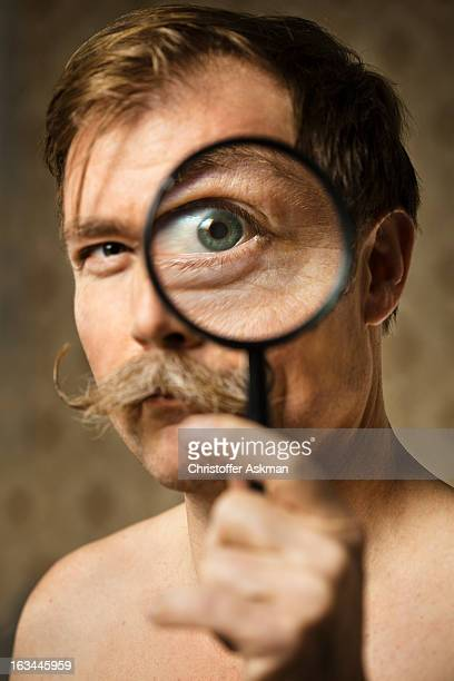 man looking in magnifying glass