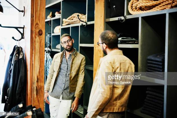 Man looking in mirror as he tries on jacket in mens clothing boutique