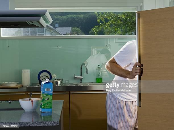 man looking in refrigerator - milk carton stock photos and pictures