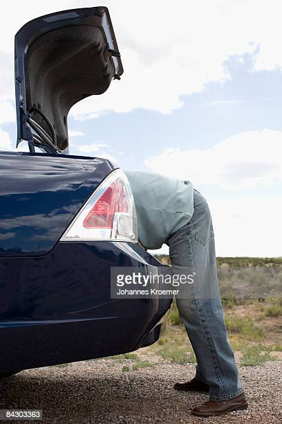 Man looking in trunk of car