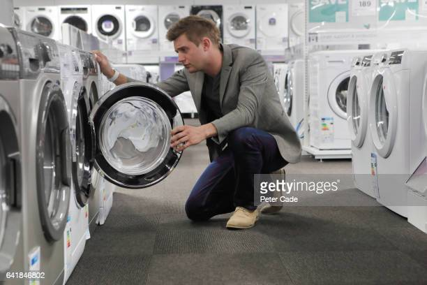 Man looking inside appliance in shop