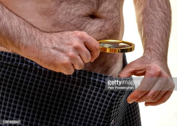man looking inside his underwear through magnify glass. - genital herpes stock-fotos und bilder