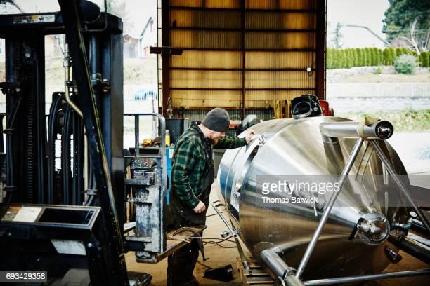 Man looking inside stainless steel tank before beginning weld project in metal workshop