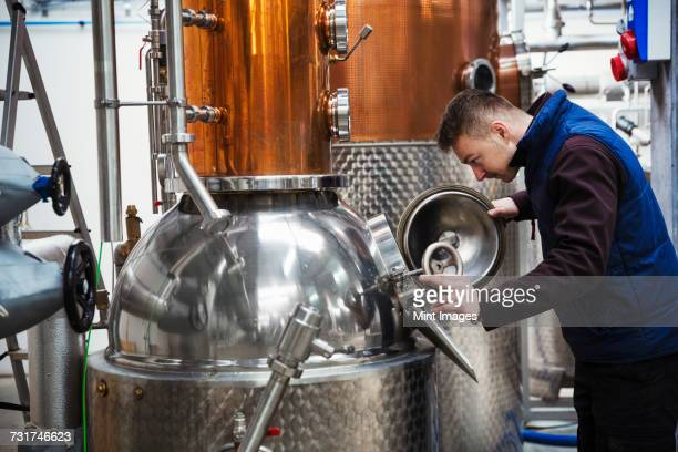 man looking into a metal tank in a distillery. - brewery stock pictures, royalty-free photos & images