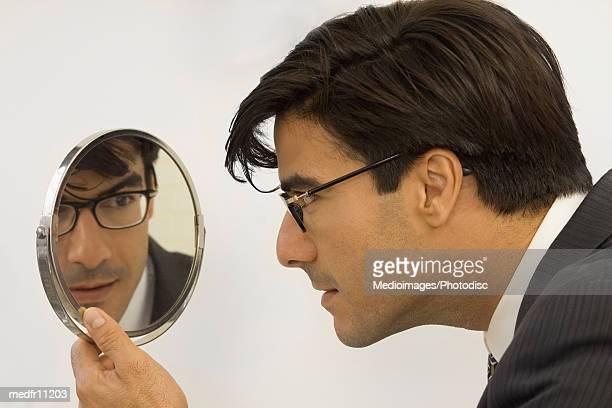 a man looking into a mirror - hand mirror stock pictures, royalty-free photos & images