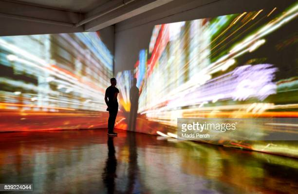 man looking into a nighttime cityscape being projected in gallery space - innovation stock pictures, royalty-free photos & images