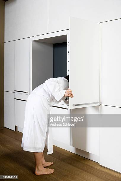 A man looking into an opened cabinet