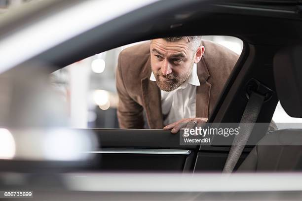 Man looking into car in car dealership