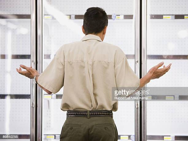 man looking into empty refrigerators at market - sold out stock pictures, royalty-free photos & images