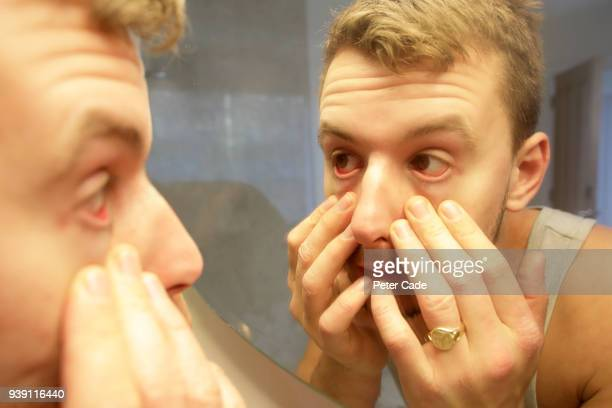 man looking into eyes in mirror - bloodshot stock pictures, royalty-free photos & images