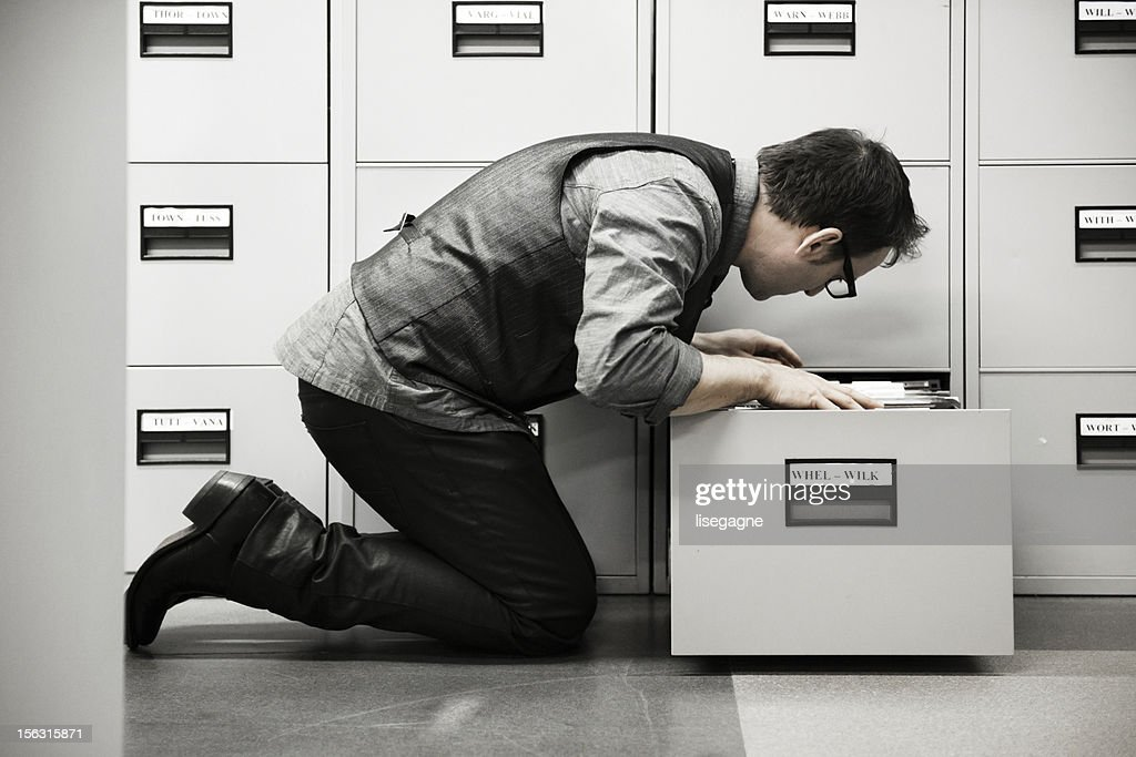 Man looking into filing cabinet : Stock Photo