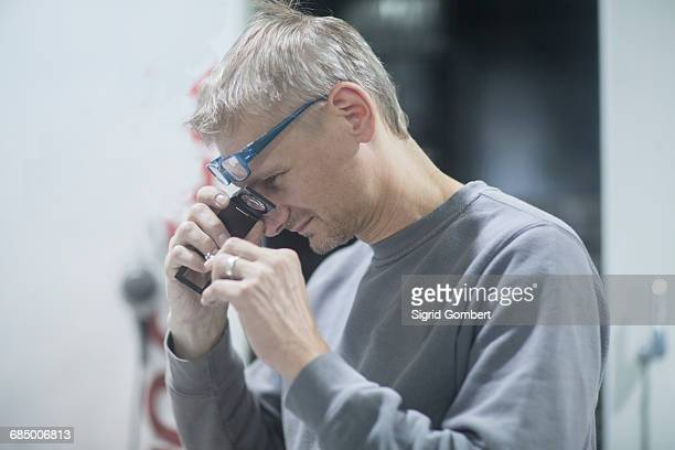 man looking into magnifying loupe - sigrid gombert stock-fotos und bilder