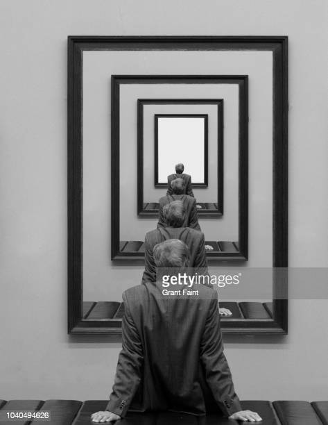 man looking into picture frame. - art stock pictures, royalty-free photos & images