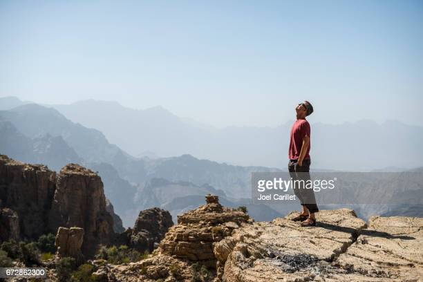 Man looking into sky in mountains of Oman