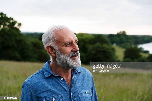 man looking off camera in meadow - one man only stock pictures, royalty-free photos & images