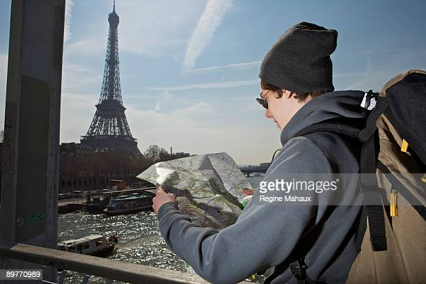 Man looking on the map near eiffel tower
