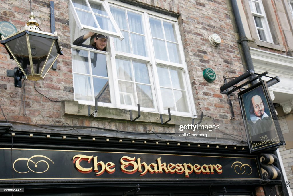 A Man Looking Out A Window Above The Shakespeare Pub On Saddler
