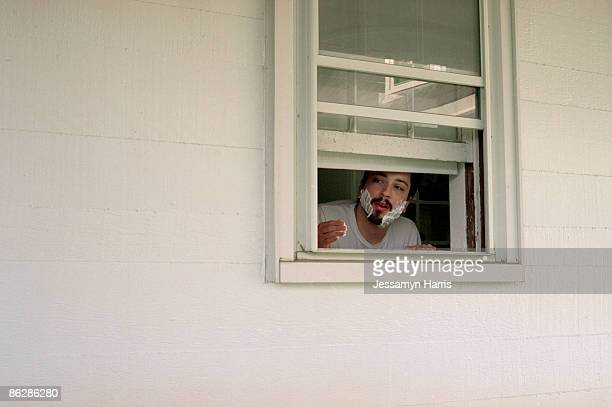 man looking out a window with shaving cream on his face - jessamyn harris stock pictures, royalty-free photos & images