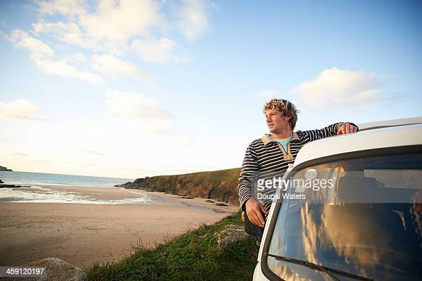 Man looking out along coastline from camper van.