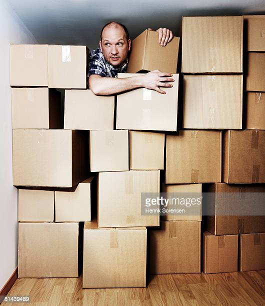 Man looking out from a room filled with boxes
