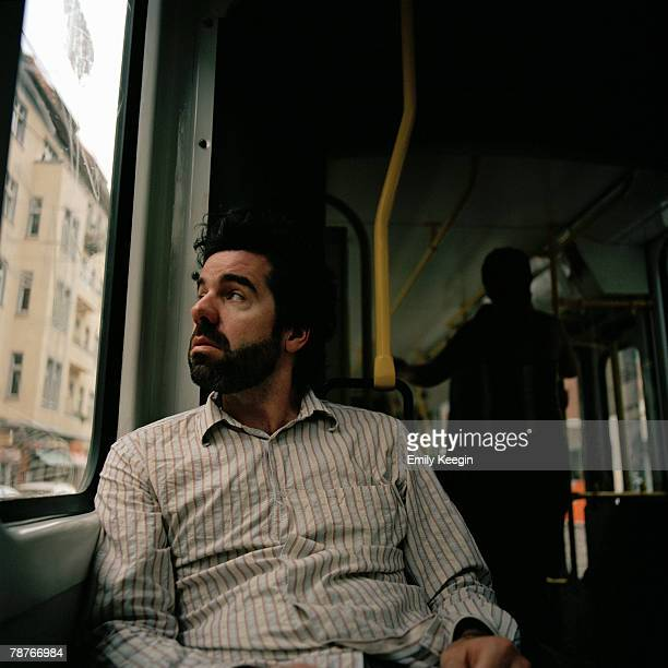 A man looking out of a bus window