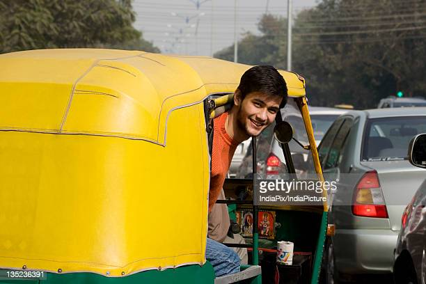 man looking out of an auto rickshaw - auto rickshaw stock pictures, royalty-free photos & images