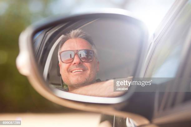 man looking out of car window - vehicle mirror stock photos and pictures