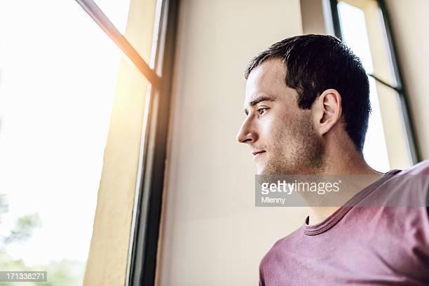 Mann schaut aus dem Fenster