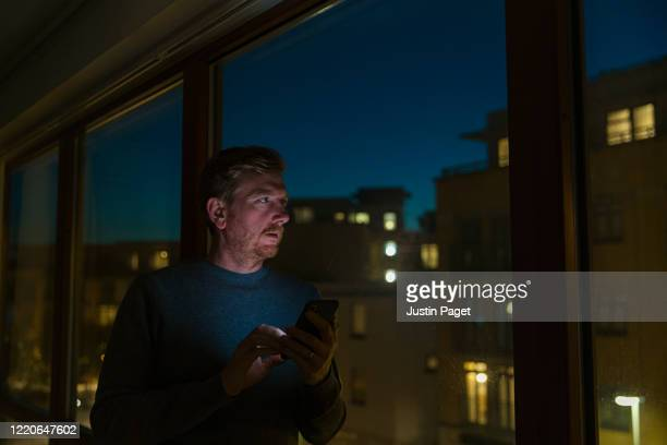 man looking out of window - dusk - night stock pictures, royalty-free photos & images