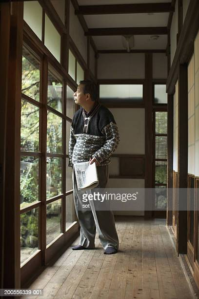 Man looking out of window in home