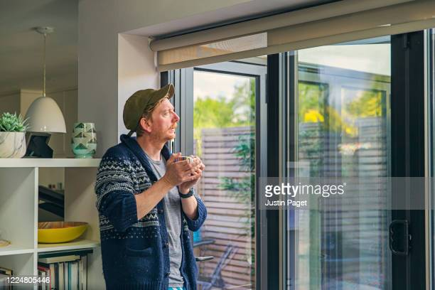 man looking out of window with a cuppa - morning stock pictures, royalty-free photos & images