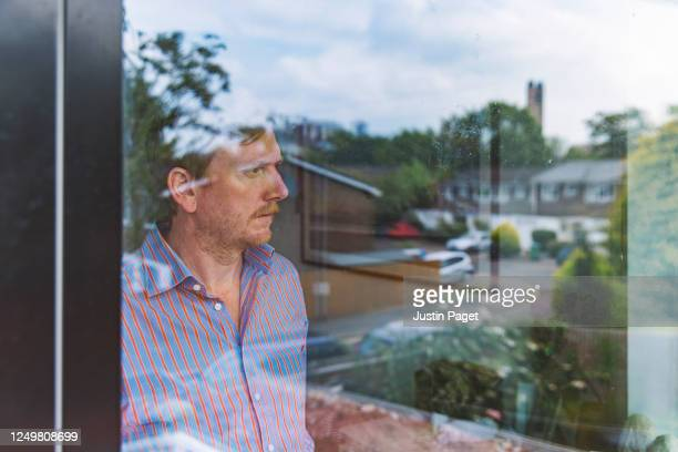 man looking out of window with a reflection suburbia - males stock pictures, royalty-free photos & images