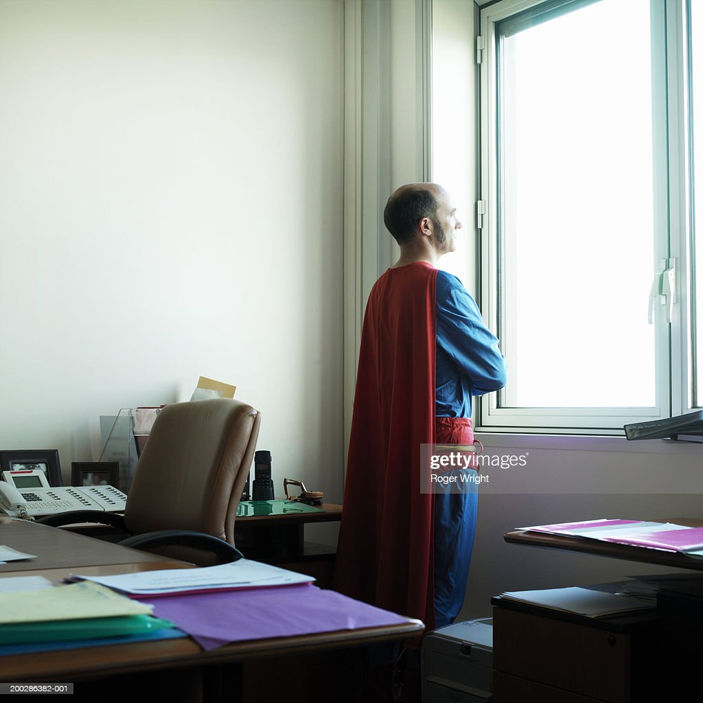Man Looking Out Office Window In Superhero Costume : Stock Photo