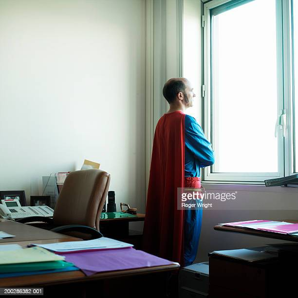 Man looking out office window in superhero costume