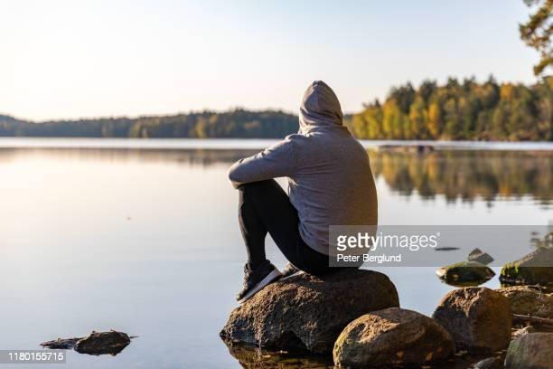 man kijkt uit over een meer - mindfulness stockfoto's en -beelden